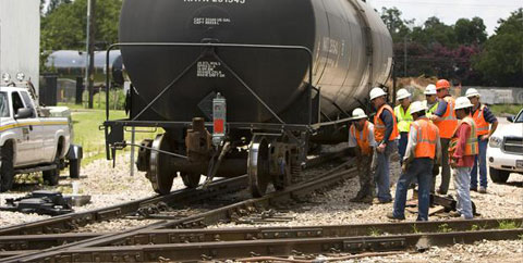 Railroad workers inspect tracks at the scene of a Capital Metro freight locomotive derailment in Austin, TX