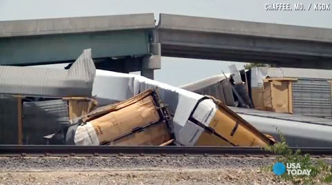 Rail cars and a concrete roadway lay in a heap after a collision between a Union Pacific train and a BNSF train caused a highway overpass to collapse in Rockview, MO on May 25, 2013. The accident injured several motorists.